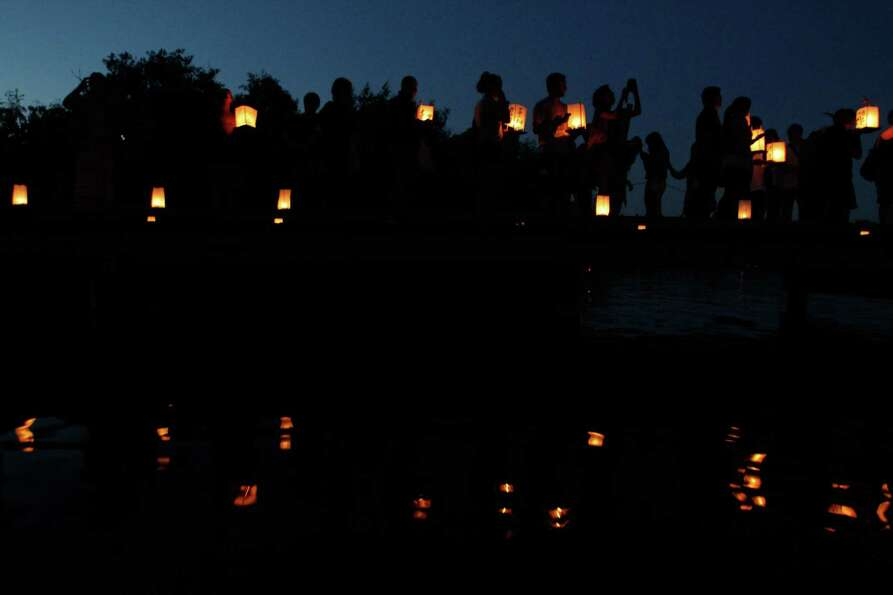 People wait in line on a dock to release floating lanterns into Green Lake during the From Hiroshima