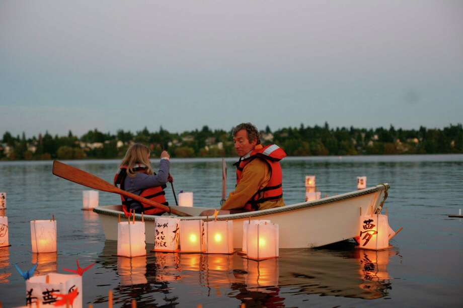 People row a boat as lanterns float by  during the From Hiroshima to Hope Latern Ceremony held at Green Lake on Monday, Aug. 6, 2012. From Hiroshima to Hope is an annual Lantern Floating Ceremony which is held to promote peace and remember victims of Hiroshima/Nagasaki and all victims of war. Photo: Sofia Jaramillo / SEATTLEPI.COM