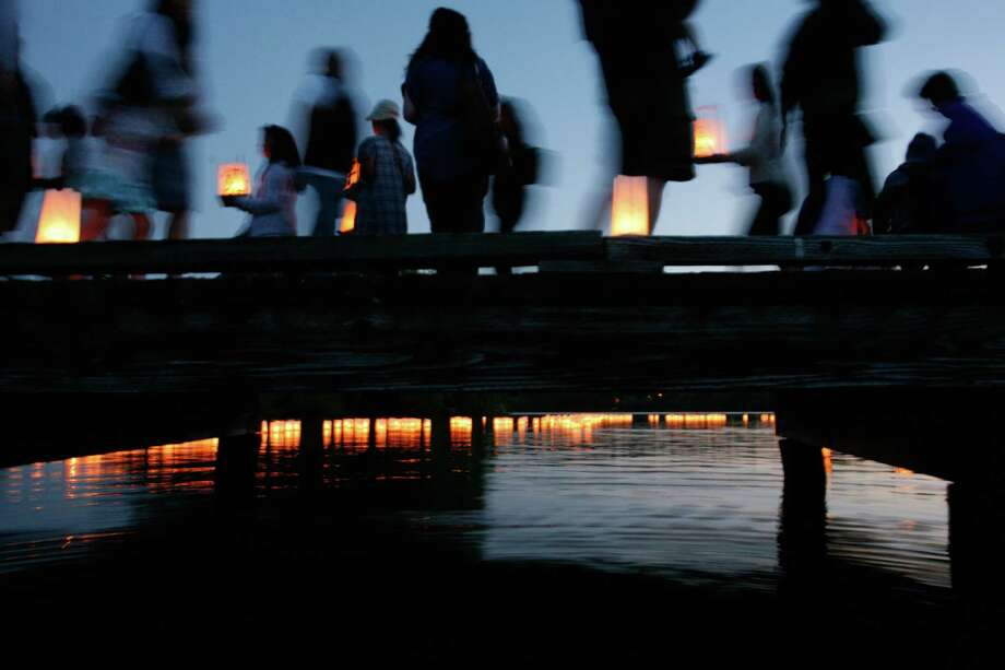 People walk out on a dock to release floating lanterns in the water during the From Hiroshima to Hope Latern Ceremony held at Green Lake on Monday, Aug. 6, 2012. From Hiroshima to Hope is an annual Lantern Floating Ceremony which is held to promote peace and remember victims of Hiroshima/Nagasaki and all victims of war. Photo: Sofia Jaramillo / SEATTLEPI.COM