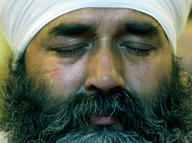 A tear runs down the cheek of a member of the Sikh Temple of Wisconsin as he attends a news conference at Oak Creek Centennial church in Oak Creek, Wis. on Monday, Aug 6, 2012. Officials and witnesses said a gunman walked into the temple on Sunday, Aug. 5, 2012 and opened fire as several dozen people prepared for Sunday morning services. Six were killed, and three were critically wounded. (AP Photo/Jeffrey Phelps) Photo: Jeffrey Phelps