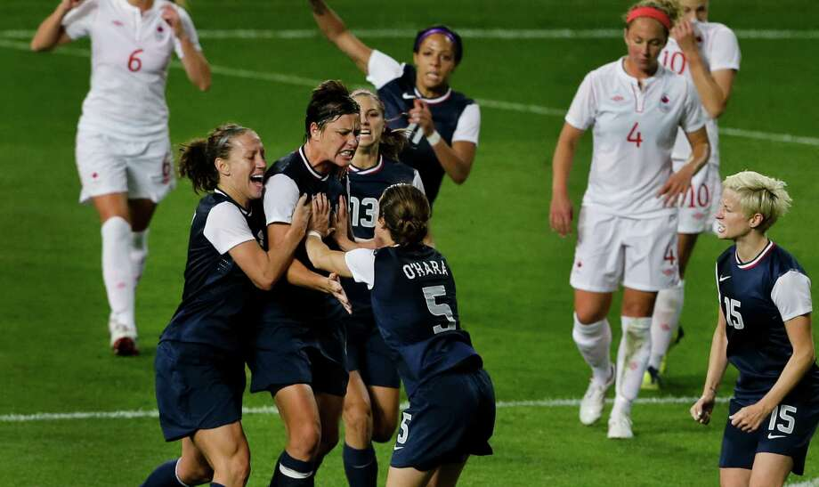 United States' Abby Wambach, center-left, is congratulated by her team after scoring on a penalty during the semifinal women's soccer match between the USA and Canada in the 2012 Summer Olympics, Monday, Aug. 6, 2012, at Old Trafford in Manchester, England. Photo: Ben Curtis, AP / AP