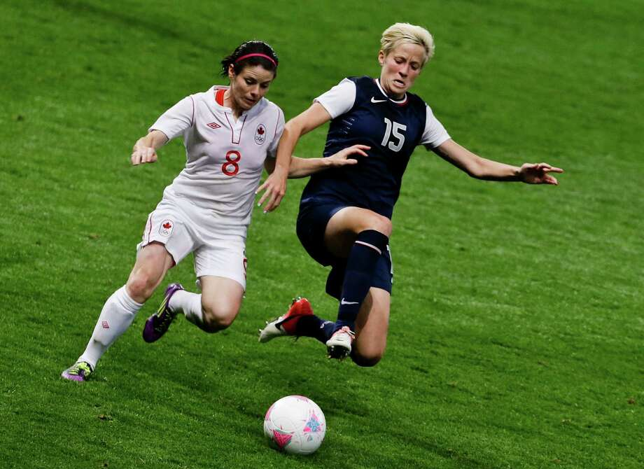 Canada's Diana Matheson, left, and United States' Megan Rapinoe, right, compete for the ball during the semi-final women's soccer match between the USA and Canada in the 2012 Summer Olympics, Monday, Aug. 6, 2012, at Old Trafford in Manchester, England. Photo: Ben Curtis, AP / AP