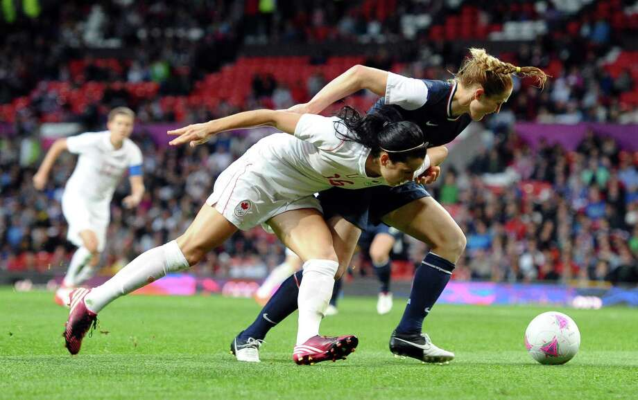 Canada's forward Jonelle Filigno (L) and United States's defender Rachel Buehler compete during the London 2012 Olympic women's football semi final match between USA and Canada at Old Trafford in Manchester, north-west England, on August 6, 2012.  AFP PHOTO/PAUL ELLISPAUL ELLIS/AFP/GettyImages Photo: PAUL ELLIS, AFP/Getty Images / AFP
