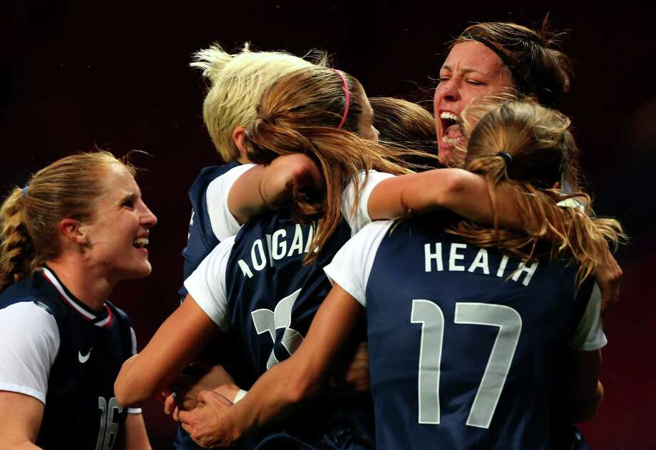 MANCHESTER, ENGLAND - AUGUST 06:  Alex Morgan #13 of the United States celebrates with her team-mates after scoring the winning goal in extra time during the Women's Football Semi Final match between Canada and USA, on Day 10 of the London 2012 Olympic Games at Old Trafford on August 6, 2012 in Manchester, England. Photo: Stanley Chou, Getty Images / 2012 Getty Images