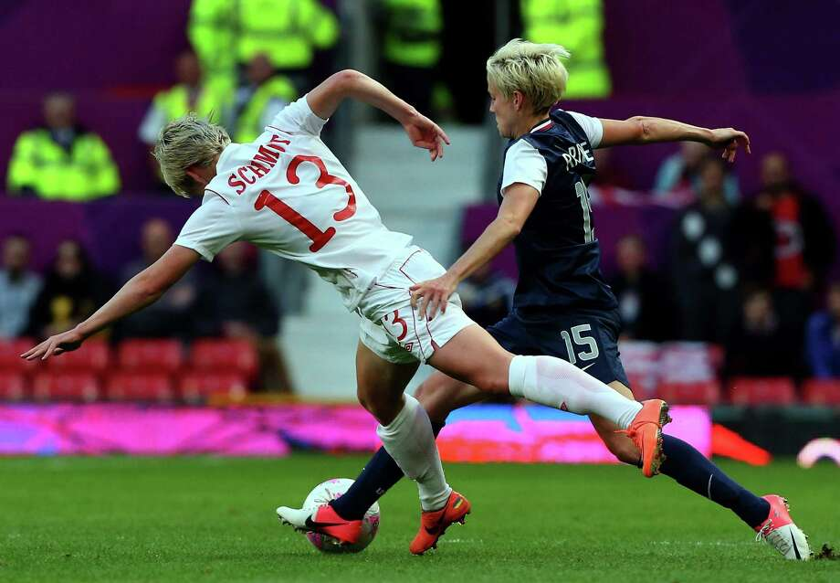 MANCHESTER, ENGLAND - AUGUST 06:  Megan Rapinoe of the United States clashes with Sophie Schmidt of Canada during the Women's Football Semi Final match between Canada and USA, on Day 10 of the London 2012 Olympic Games at Old Trafford on August 6, 2012 in Manchester, England. Photo: Stanley Chou, Getty Images / 2012 Getty Images