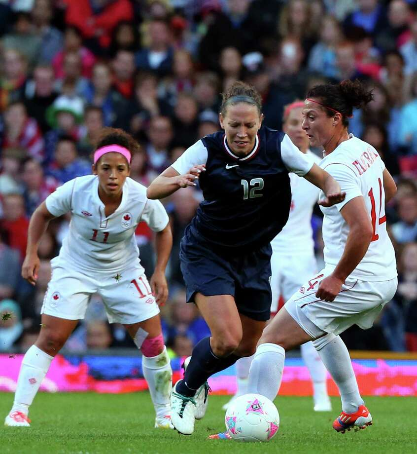 MANCHESTER, ENGLAND - AUGUST 06: Lauren Cheney of United States  battles with Melissa Tancredi of Canada during the Women's Football Semi Final match between Canada and USA, on Day 10 of the London 2012 Olympic Games at Old Trafford on August 6, 2012 in Manchester, England. Photo: Stanley Chou, Getty Images / 2012 Getty Images