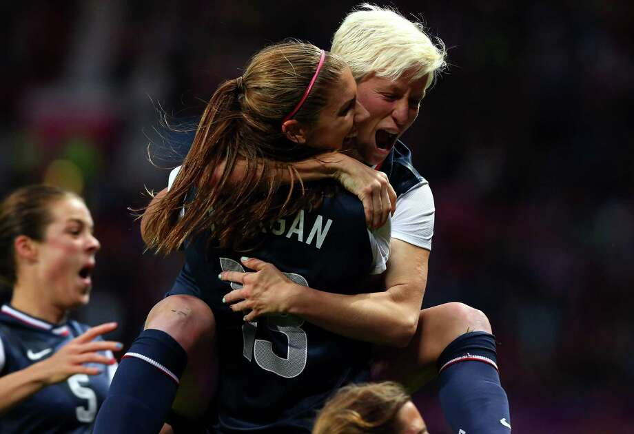 MANCHESTER, ENGLAND - AUGUST 06:  Megan Rapinoe  celebrates with Alex Morgan of the United States after scoring during the Women's Football Semi Final match between Canada and USA, on Day 10 of the London 2012 Olympic Games at Old Trafford on August 6, 2012 in Manchester, England. Photo: Stanley Chou, Getty Images / 2012 Getty Images