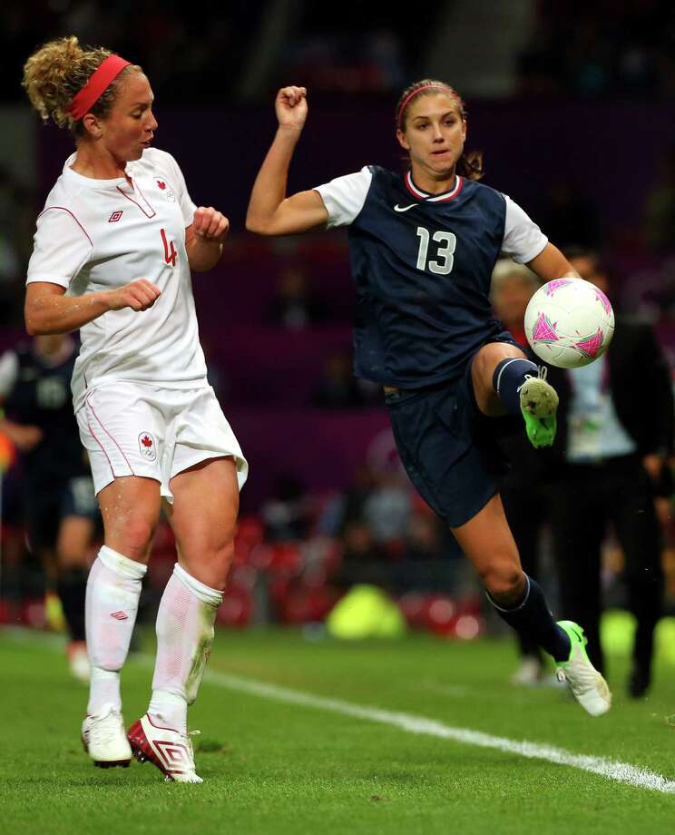 MANCHESTER, ENGLAND - AUGUST 06:  Alex Morgan of the United States is challenged by Carmelina Moscato of Canada during extra time during the Women's Football Semi Final match between Canada and USA, on Day 10 of the London 2012 Olympic Games at Old Trafford on August 6, 2012 in Manchester, England. Photo: Stanley Chou, Getty Images / 2012 Getty Images