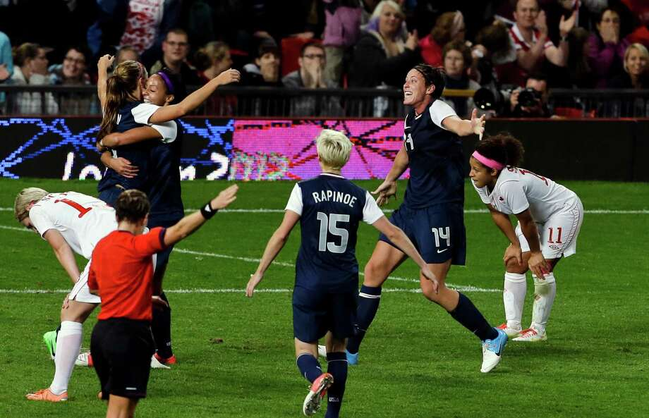 The United States' Alex Morgan, far left, is hugged by the United States' Sydney Leroux, as she celebrates her goal in the final minutes of extra time with United States' Abby Wambach (14), and United States' Megan Rapinoe, center, which gave the USA a 4-3 victory in the semi-final women's soccer match between the USA and Canada in the 2012 Summer Olympics, Monday, Aug. 6, 2012, at Old Trafford in Manchester, England. Photo: Ben Curtis, AP / AP