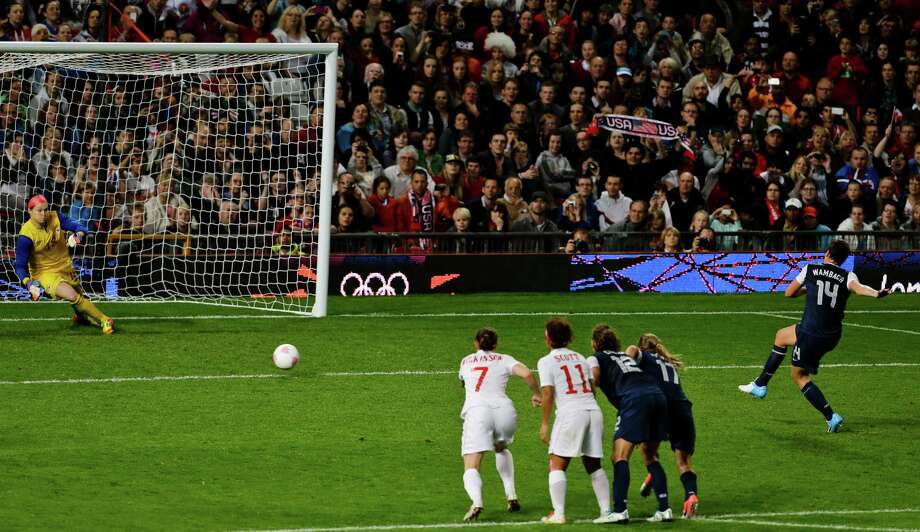 The United States' Abby Wambach, right, scores a penalty past Canada's goalkeeper Erin Mcleod, left, during the semifinal women's soccer match between the USA and Canada in the 2012 Summer Olympics, Monday, Aug. 6, 2012, at Old Trafford in Manchester, England. Photo: Ben Curtis, AP / AP