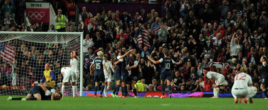 US footballers celebrate scoring the winning goal during injury time of extra time during the London 2012 Olympic women's football semi final match between USA and Canada at Old Trafford in Manchester, north-west England, on August 6, 2012.  US won 4-3. AFP PHOTO/PAUL ELLISPAUL ELLIS/AFP/GettyImages Photo: PAUL ELLIS, AFP/Getty Images / AFP