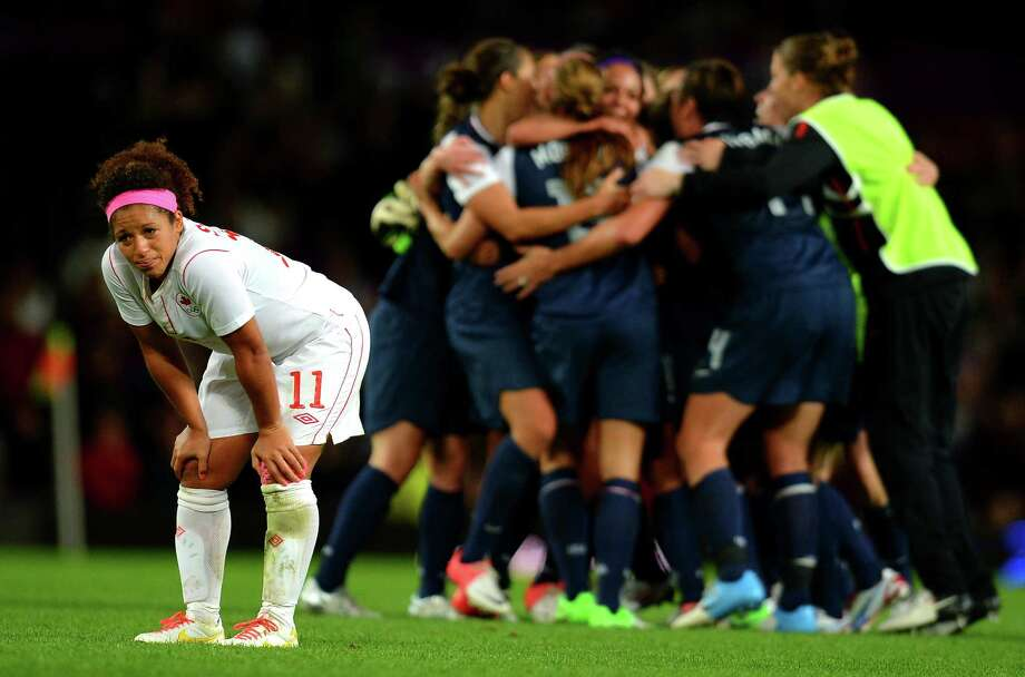 Canada's midfielder Desiree Scott (L) reacts as the US team celebrates after the London 2012 Olympic Games women's semi final football match between the US and Canada at Old Trafford in Manchester, north-west England on August 6, 2012. AFP PHOTO / ANDREW YATESANDREW YATES/AFP/GettyImages Photo: ANDREW YATES, AFP/Getty Images / AFP