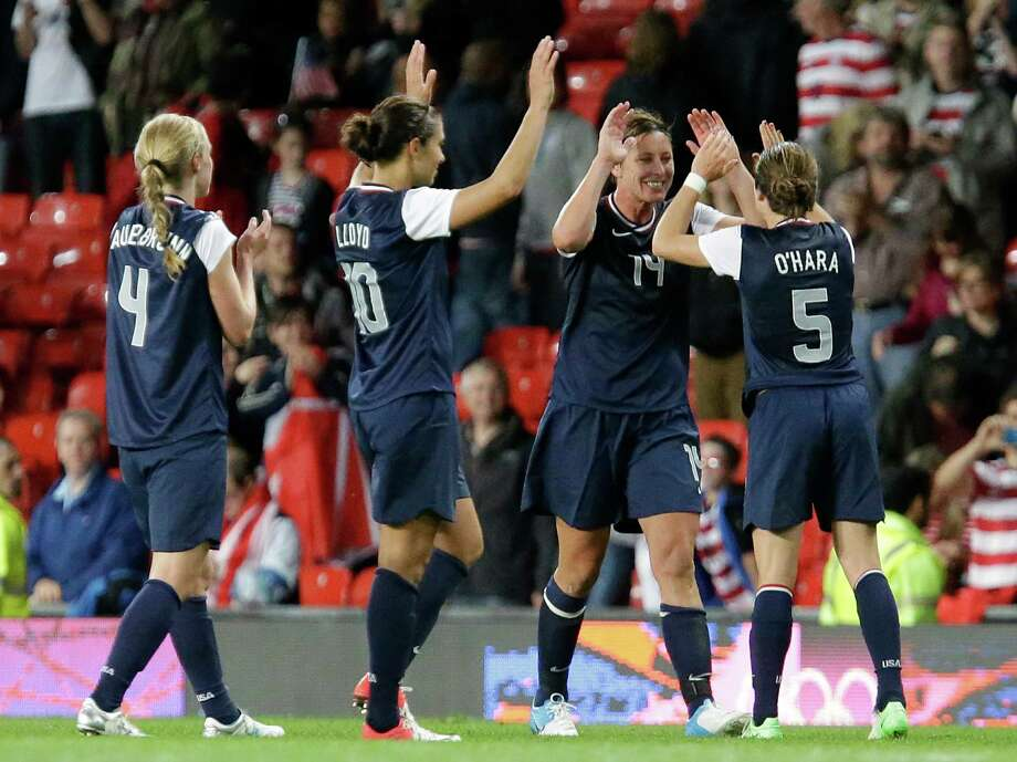 United States' players celebrate after defeating Canada in their semifinal women's soccer match at the 2012 London Summer Olympics, in Manchester, England, Monday, Aug. 6, 2012. Photo: Hussein Malla, AP / AP