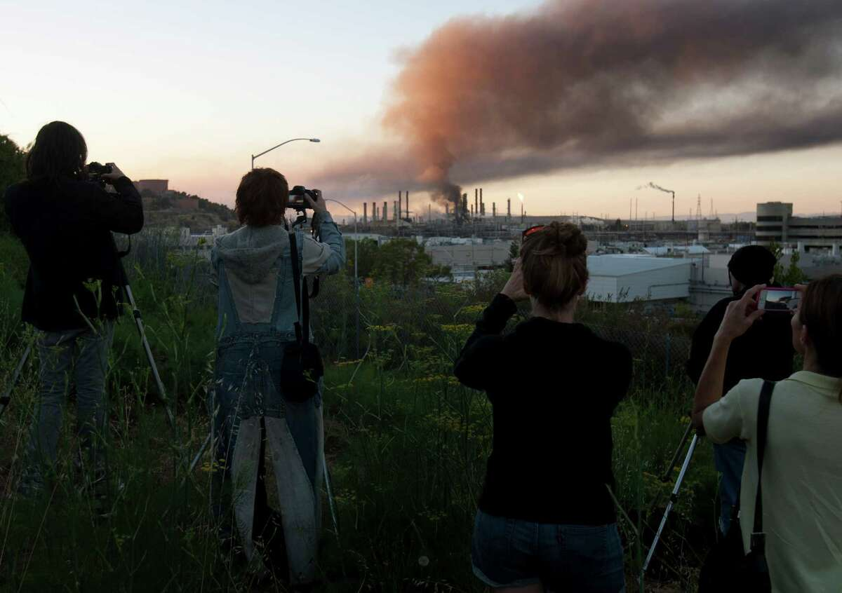 The curious gather on a hillside in Point Richmond, Calif., to photograph the the fire in an oil unit at the Chevron refinery in Richmond, Calif., Monday. Officials told residents of two Northern California cities to shelter-in-place as a fire at a Chevron refinery in Richmond releases plumes of black smoke. (AP Photo/D. Ross Cameron/) (AP Photo/The Contra Costa Times, D. Ross Cameron)