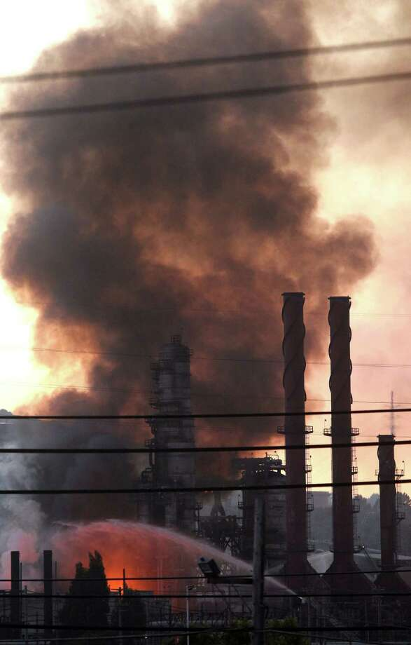 Fire crews pour water on a fire at the Chevron Richmond Refinery in Richmond, Calif., Monday. Officials told residents of two Northern California cities to shelter-in-place as a fire at the refinery released plumes of black smoke. The fire, first reported at 6:40 p.m. Monday, was burning in a process unit at the refinery, officials said. It was sending smoke over the cities of Richmond and San Pablo. (AP Photo/San Francisco Chronicle, Lance Iversen)  Photo: Ap/getty