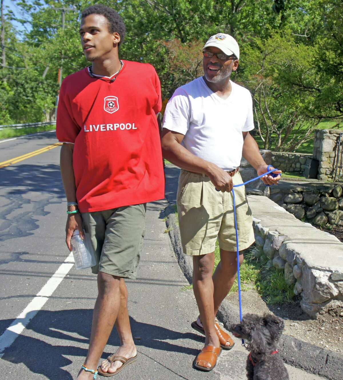 Dennis Ray, right, and his son, Raphael, take an afternoon walk past Harvey Weinstein's house on Beachside Avenue, ahead of the evening visit of President Barack Obama to Weinstein's home. Monday, Aug. 6, 2012/ Westport, CT