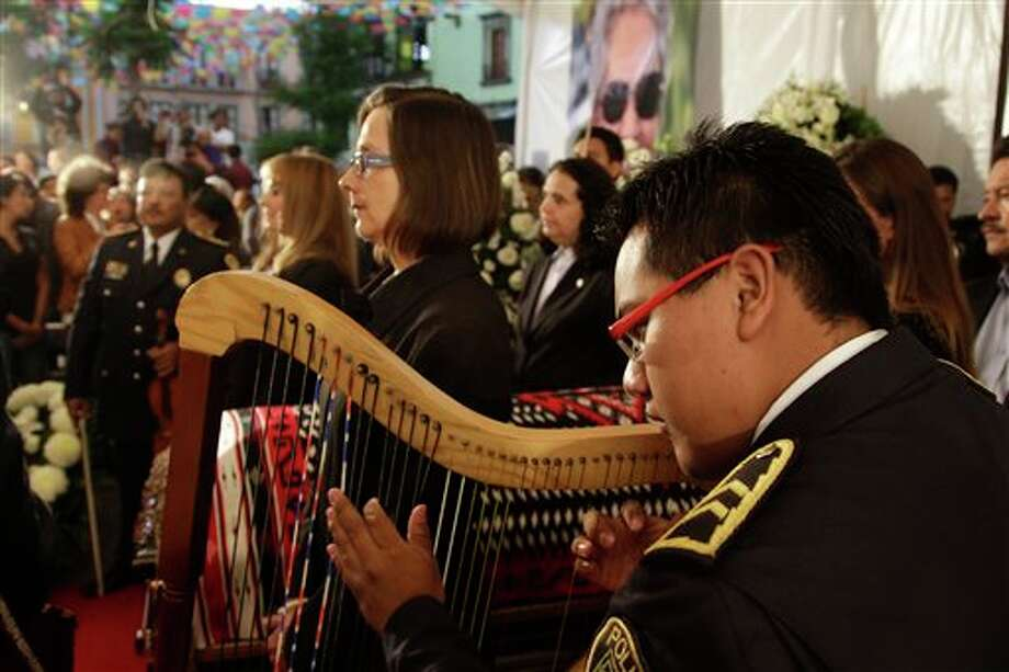 Mariachi musicians perform as city officials stand at honor guard next to the coffin of famed Mexican singer Chavela Vargas during a homage at the traditional Mariachi Garibaldi Plaza in Mexico City, Monday, Aug. 6, 2012. Chavela Vargas, who defied gender stereotypes to become one of the most legendary singers in Mexico, died Aug. 5 at age 93. Photo: Dario Lopez-Mills, AP / AP