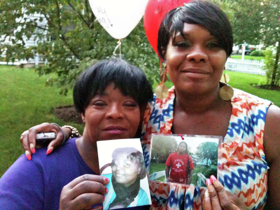 Barbara Smalls, of Norwalk, left, and April Barron of Bridgeport, hold photos of Rickita Smalls and Iroquois Alston, who were shot to death a year ago Monday in Norwalk, during a remembrance ceremony held a the site of the crime. Photo: Andrew Brophy