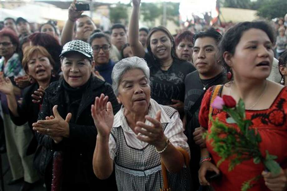 People sing and cheer during a homage to famed Mexican singer Chavela Vargas at the traditional Mariachi Garibaldi Plaza in Mexico City, Monday, Aug. 6, 2012. Chavela Vargas, who defied gender stereotypes to become one of the most legendary singers in Mexico, died Aug. 5 at age 93. Photo: Eduardo Verdugo, AP / AP