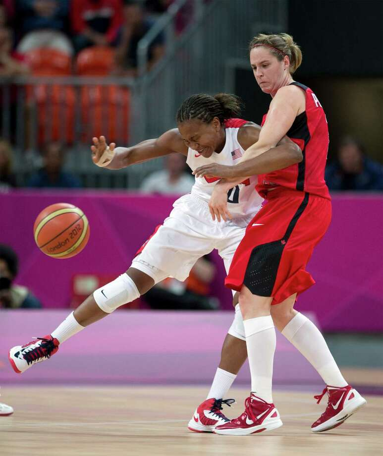 USA's Tamika Catchings, left, collides with Canada's Courtnay Pilypaitis while chasing the ball during a women's basketball game at the 2012 Summer Olympics, Tuesday, Aug. 7, 2012, in London. (AP) Photo/The Canadian Press, Frank Gunn) Photo: Frank Gunn, Associated Press / CP