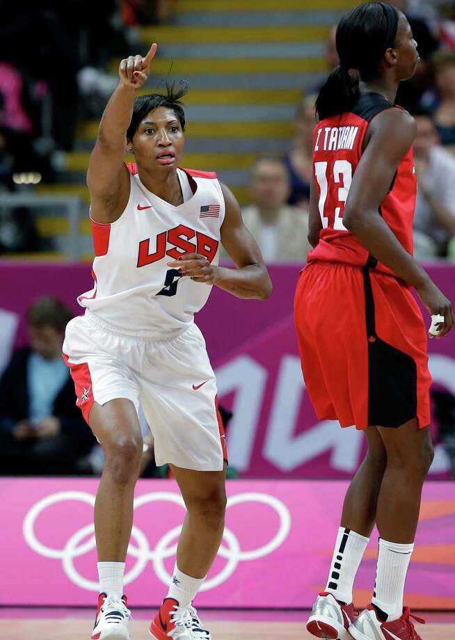 USA's Angel McCoughtry, left, runs past Canada's Tamara Tatham as she celebrates a score during a quarterfinal women's basketball game at the 2012 Summer Olympics, Tuesday, Aug. 7, 2012, in London. (AP Photo/Eric Gay) Photo: Eric Gay, Associated Press / AP