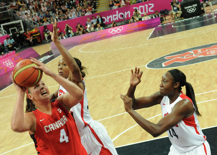 Canadian centre Krista Phillips (L) vies with US forward Tamika Catchings (C) and US centre Tina Charles during the women's quarter final basketball match USA vs Canada at the London 2012 Olympic Games on August 7, 2012 at the North Greenwich arena in London. AFP PHOTO / POOL / Mark RALSTONMARK RALSTON/AFP/GettyImages Photo: MARK RALSTON, AFP/Getty Images / AFP