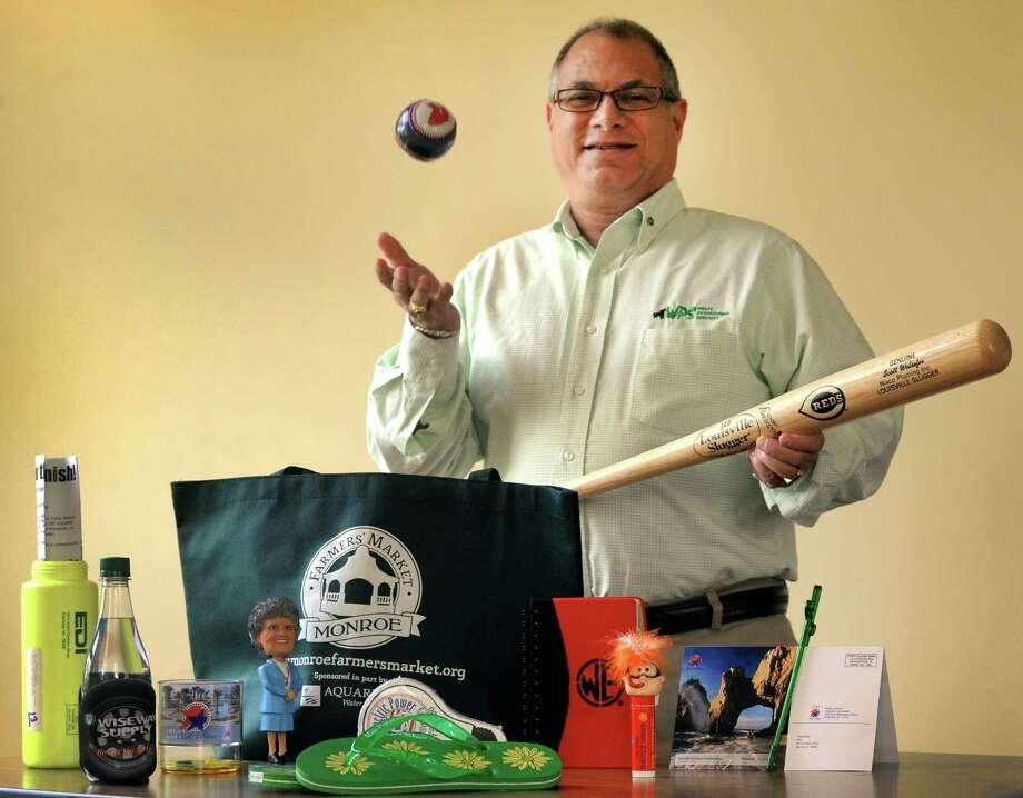 Dave Wolfe of Wolfe Promotional Services shows off some of the unique items he offers to customers. Some of the promotional items and business gifts he offers include personalized bobbleheads, tote bags, flip-flops mailings in unique packaging and personalized baseball bats. Photo: Cathy Zuraw / Connecticut Post