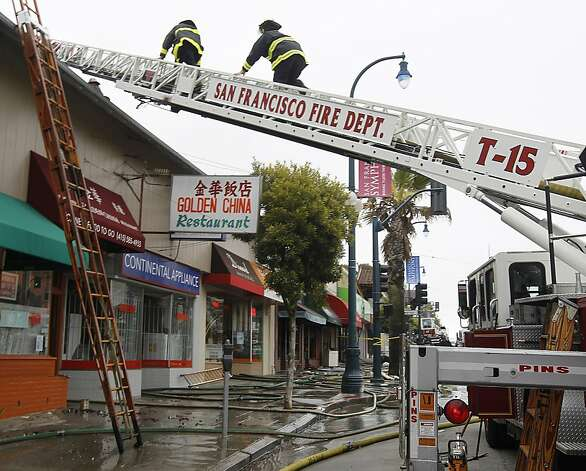 Firefighters climb a ladder to clean up after a four-alarm fire heavily damaged three businesses on the 1500 block of Ocean Avenue in San Francisco, Calif. on Tuesday, Aug. 7, 2012. Photo: Paul Chinn, The Chronicle