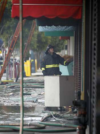 A firefighter surveys the damage from a four-alarm fire that gutted three businesses on the 1500 block of Ocean Avenue in San Francisco, Calif. on Tuesday, Aug. 7, 2012. Photo: Paul Chinn, The Chronicle