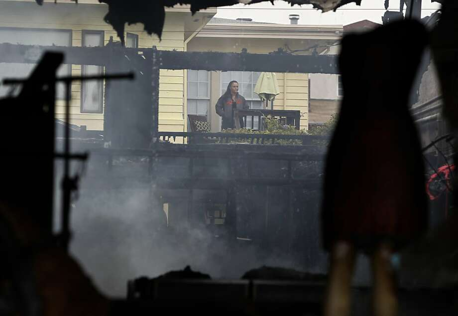 A neighbor views the damage from her backyard deck after a four-alarm fire gutted three businesses, including the Lili Knit clothing and fabric store, on the 1500 block of Ocean Avenue in San Francisco, Calif. on Tuesday, Aug. 7, 2012. Photo: Paul Chinn, The Chronicle