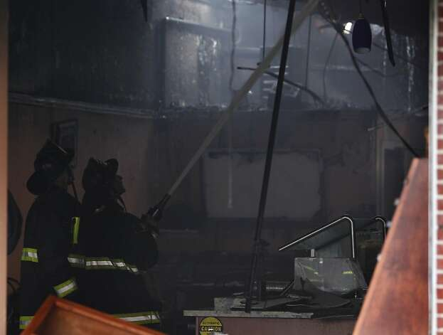 Firefighters douse hot spots inside King's Coffee shop after a four-alarm fire heavily damaged three businesses on the 1500 block of Ocean Avenue in San Francisco, Calif. on Tuesday, Aug. 7, 2012. Photo: Paul Chinn, The Chronicle