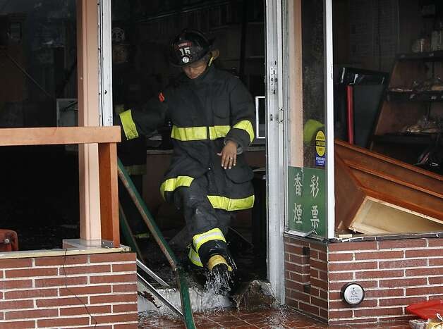 A firefighter walks out of King's Coffee shop after a four-alarm fire heavily damaged three businesses on the 1500 block of Ocean Avenue in San Francisco, Calif. on Tuesday, Aug. 7, 2012. Photo: Paul Chinn, The Chronicle