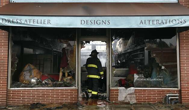 A firefighter views the damage inside the Lili Knit clothing shop after a four-alarm fire gutted three businesses on Ocean Avenue. Photo: Paul Chinn, The Chronicle