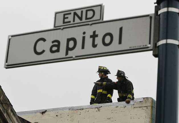 Firefighters work on the roof after battling a four-alarm fire that heavily damaged three businesses at Ocean Avenue and Capitol Street in San Francisco, Calif. on Tuesday, Aug. 7, 2012. Photo: Paul Chinn, The Chronicle