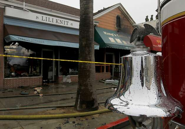 Firefighters clean up after a four-alarm fire heavily damaged three businesses on the 1500 block of Ocean Avenue in San Francisco, Calif. on Tuesday, Aug. 7, 2012. Photo: Paul Chinn, The Chronicle