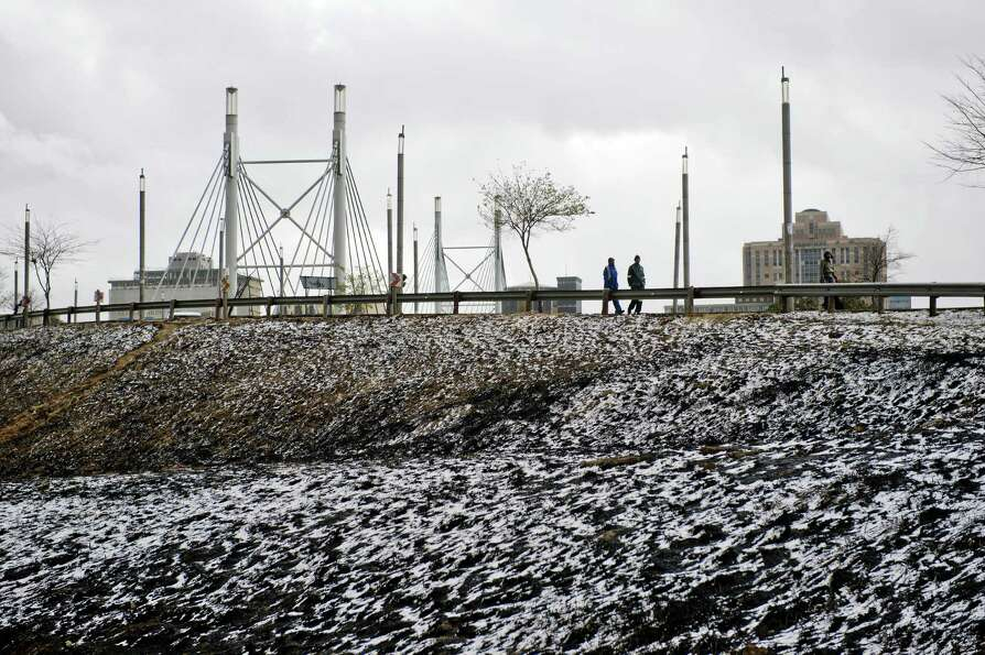 Two people walk in the snow near Nelson Mandela bridge on August 7, 2012 in Johannesburg. Snow falls