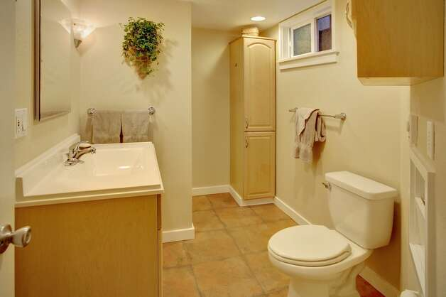 Bathroom of 2152 N.E. 102nd St. The 2,920-square-foot house, built in 1946, has three bedrooms, 1.75 bathrooms, an updated kitchen, lots of windows, a basement rec room with a bar and fireplace, a patio and gardens on a 9,783-square-foot corner lot. It's listed for $485,000. Photo: Courtesy Gary Everist/Windermere Real Estate