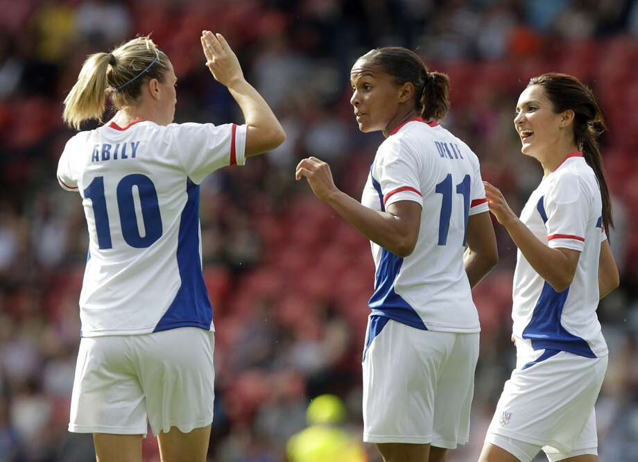 France's Marie-Laure Delie (2ndL) is congratulated by teammates Camille Abily (L) and Louisa Necib (R) after scoring a goal during the Olympic Women's football match France vs. USA at Hampden Park, Glasgow, Scotland, on July 25, 2012, as part of the London 2012 Olympic games.  AFP PHOTO/GRAHAM STUART        (Photo credit should read GRAHAM STUART/AFP/GettyImages) (AFP/Getty Images)