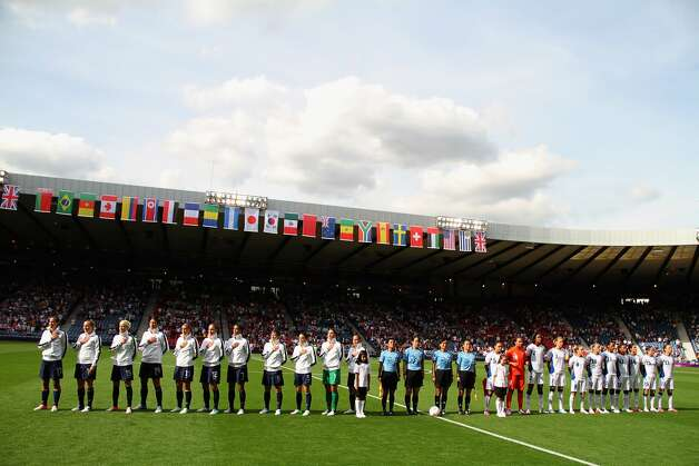 GLASGOW, SCOTLAND - JULY 25:  USA sings their national anthem while France looks on during the Women's Football first round Group G Match of the London 2012 Olympic Games between United States and France, at Hampden Park on July 25, 2012 in Glasgow, Scotland.  (Photo by Stanley Chou/Getty Images) (Stanley Chou / Getty Images)