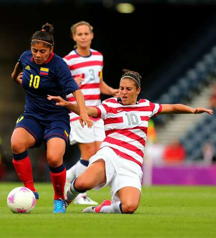 GLASGOW, SCOTLAND - JULY 28: Carli Lloyd of USA tackles Maria Usma of Columbia during the Women's Football first round Group G match between United States and Colombia on Day 1 of the London 2012 Olympic Games at Hampden Park on July 28, 2012 in Glasgow, Scotland.  (Photo by Stanley Chou/Getty Images) (Getty Images)