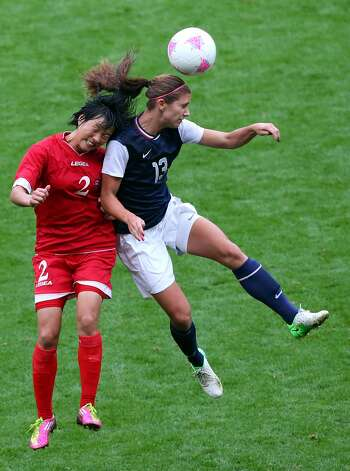 MANCHESTER, ENGLAND - JULY 31:  Alex Morgan of USA clashes with Kim Myong Gum of DPR Korea during the Women's Football first round Group G match between the United States and DPR Korea,on Day 4 of the London 2012 Olympic Games at Old Trafford on July 31, 2012 in Manchester, England.  (Photo by Stanley Chou/Getty Images) (Getty Images)