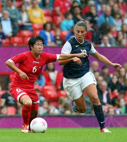 MANCHESTER, ENGLAND - JULY 31:  Carli Lloyd of United States battles with Choe Un Ju of DPR Korea during the Women's Football first round Group G match between the United States and DPR Korea,on Day 4 of the London 2012 Olympic Games at Old Trafford on July 31, 2012 in Manchester, England.  (Photo by Stanley Chou/Getty Images) (Getty Images)