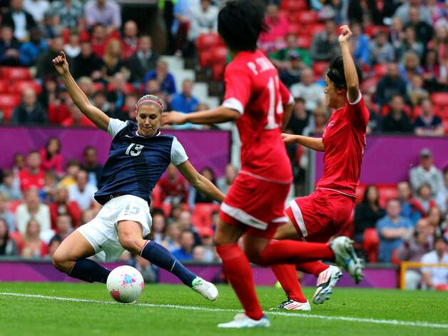 MANCHESTER, ENGLAND - JULY 31: Alex Morgan of USA strikes the ball while Kim Myong Gum and Pong Son Hwa (14) of DPR Korea during the Women's Football first round Group G match between the United States and DPR Korea,on Day 4 of the London 2012 Olympic Games at Old Trafford on July 31, 2012 in Manchester, England.  (Photo by Stanley Chou/Getty Images) (Stanley Chou / Getty Images)