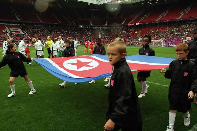 MANCHESTER, ENGLAND - JULY 31:  Children carry the national flag of DPR Korea before kick off during the Women's Football first round Group G match between the United States and DPR Korea,on Day 4 of the London 2012 Olympic Games at Old Trafford on July 31, 2012 in Manchester, England.  (Photo by Stanley Chou/Getty Images) Photo: Stanley Chou, Getty Images / 2012 Getty Images