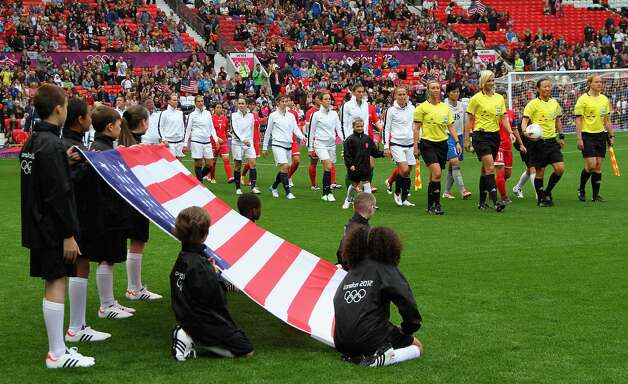 MANCHESTER, ENGLAND - JULY 31:  USA. match officials and DPR Korea enters the field with children displays the USA national flag on the foreground before kick off during the Women's Football first round Group G match between the United States and DPR Korea,on Day 4 of the London 2012 Olympic Games at Old Trafford on July 31, 2012 in Manchester, England.  (Photo by Stanley Chou/Getty Images) (Stanley Chou / Getty Images)