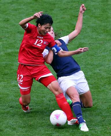 MANCHESTER, ENGLAND - JULY 31:  Kim Un Hyang of DPR Korea tackles Alex Morgan of USA during the Women's Football first round Group G match between the United States and DPR Korea on Day 4 of the London 2012 Olympic Games at Old Trafford on July 31, 2012 in Manchester, England.  (Photo by Stanley Chou/Getty Images) (Stanley Chou / Getty Images)