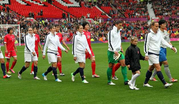 MANCHESTER, ENGLAND - JULY 31:  USA and DPR Korea enters the field during the Women's Football first round Group G match between the United States and DPR Korea on Day 4 of the London 2012 Olympic Games at Old Trafford on July 31, 2012 in Manchester, England.  (Photo by Stanley Chou/Getty Images) (Stanley Chou / Getty Images)