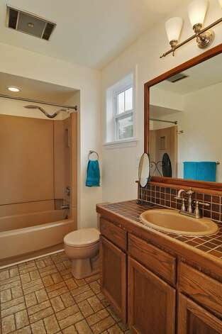 Bathroom of 11332 34th Ave. N.E. The 1,990-square-foot house, built in 1932, has four bedrooms, 2.5 bathrooms, a basement with a rec room and French doors leading to a deck on a 7,740-square-foot lot, with a shed/workshop. It's listed for $439,000. Photo: Courtesy Jill Cunningham/Windermere Real Estate