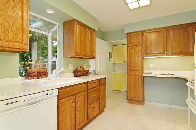 Kitchen of 11332 34th Ave. N.E. The 1,990-square-foot house, built in 1932, has four bedrooms, 2.5 bathrooms, a basement with a rec room and French doors leading to a deck on a 7,740-square-foot lot, with a shed/workshop. It's listed for $439,000. Photo: Courtesy Jill Cunningham/Windermere Real Estate