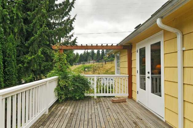 Deck of 11332 34th Ave. N.E. The 1,990-square-foot house, built in 1932, has four bedrooms, 2.5 bathrooms, a basement with a rec room and French doors on a 7,740-square-foot lot, with a shed/workshop. It's listed for $439,000. Photo: Courtesy Jill Cunningham/Windermere Real Estate